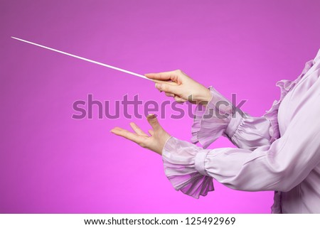 Female orchestra conductor hands, one with baton. Pink background.