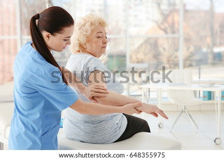 Female orthopedist examining senior woman in clinic