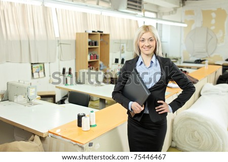 Female owner of a small business standing inside a textile factory holding a laptop computer in her hand