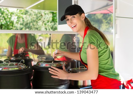 Female owner of a soup kitchen or a field kitchen stirs with a ladle in the soup