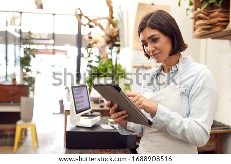 Female Owner With Digital Tablet Standing Behind Sales Desk Of Florists Store
