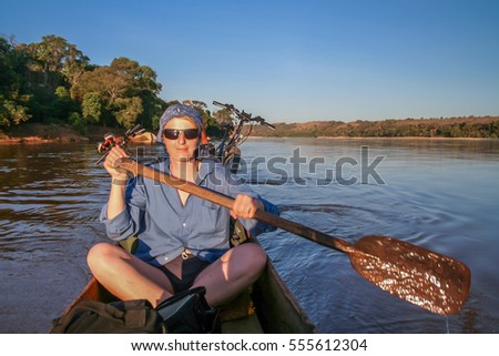 Female paddling small canoe on the Tsiribinha river in Madagascar #555612304