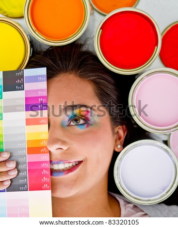 Female painter smiling with paint cans in different colors around her head