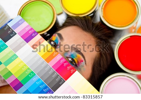 Female painter with a color palette covering her face and paint cans around her head