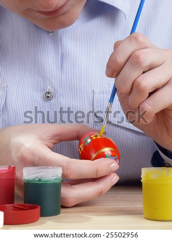 Female painting easter egg in floral patter with paintbrush