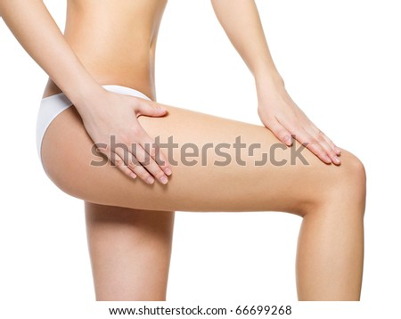 Female pampering cellulite skin on her legs - close-up shot on white background