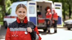Female paramedic smiling into camera, ambulance crew blurred on background