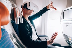 Female passenger in formal clothing spending flight time for creating 3d dimension projection in simulation cyberspace from digital VR goggles, woman in digital glasses gesturing haptic reality