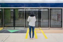 Female passenger standing on yellow line while waiting Jakarta MRT in station