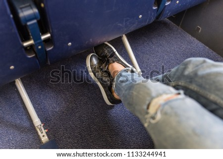 Female passenger stretching her legs on long commercial airplane flight. Exit seats with more leg space for more comfortable flight. #1133244941
