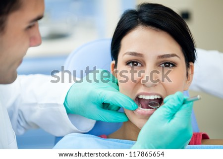 Female patient having her teeth examined by dental specialist