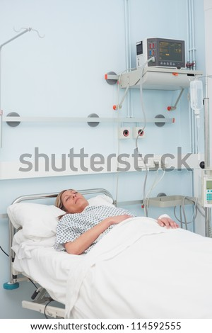 Female patient sleeping on a bed in hospital ward