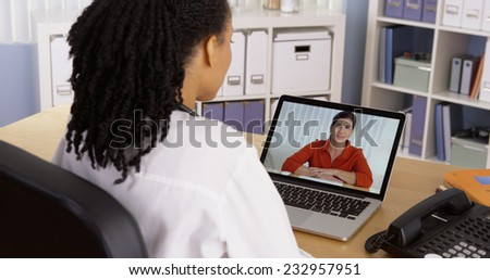 Female patient talking to African American doctor over video chat