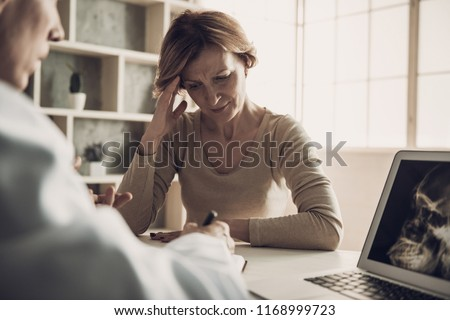 Female Patient with Ache at Doctor's Appointment. Radiologist Explain Middleaged Woman Diagnosis while Looking at X-ray Head Scan Picture at Laptop Screen. Medical Health Care Concept
