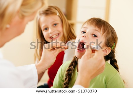 Female pediatrician doctor examining throat of a girl, in the background her sister is waiting to be examined as well