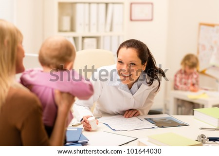 Female pediatrician smiling at baby patient sitting at office desk
