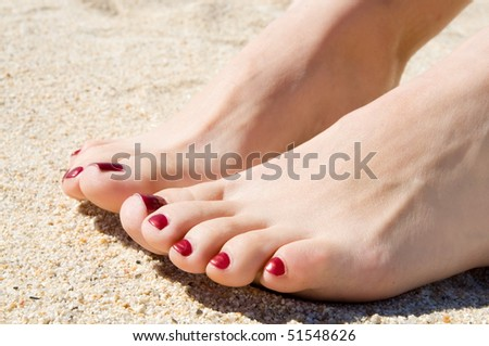 female pedicured feet on summer shore sand on sunny day