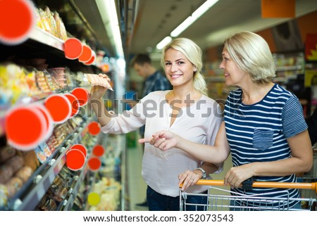 Female pensioner and her daughter choosing chilled sausages in shop