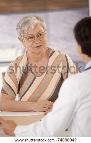 Female pensioner at doctors office listening to doctors explanation.