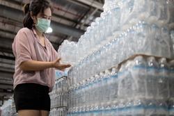 Female people choosing fresh water in plastic bottles packaged,good quality of mineral water,asian woman buying drinking water in supermarket,shopping for beverage,essential nutrition food for life