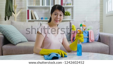 female people household cleaning lifestyle concept. happy elegant woman in rubber gloves wiping table with microfiber cloth at home wiping table. young girl holding spray face camera confident smile #1242602452