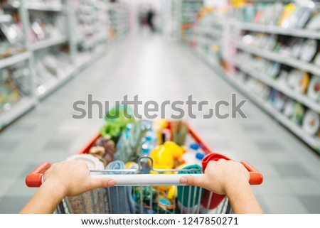 Female person hands drags the cart full of goods