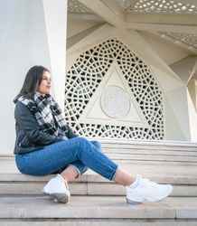 Female person in casual clothes is sitting on the stairs by the entrance of unique modern marmara university mosque. Tourist attraction in Turkey.