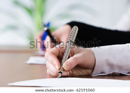 Female person's hand signing an important document