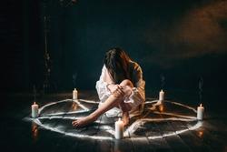 Female person sitting in pentagram circle, magic