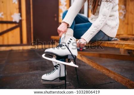 Female person sitting on bench and wears skates #1032806419