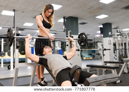 Female personal trainer helping a young man lift weights while working out in a gym