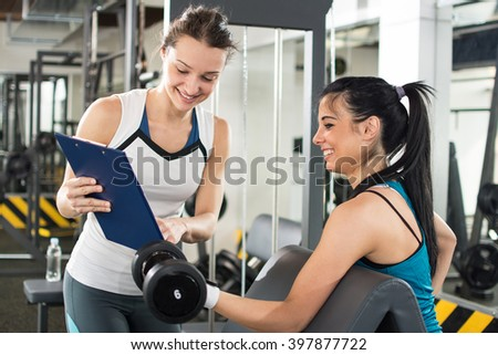 female personal trainer helping ...