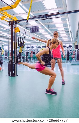 Female personal trainer teaching to woman in a hard suspension training with fitness straps on a fitness center