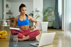 Female personal trainer using computer while holding online exercise class with her clients from home.