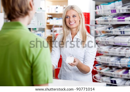 Female pharmacist giving medicine to customer at counter