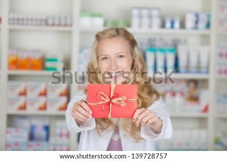Female pharmacist holding bonus coupon card gift in pharmacy