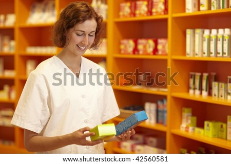 Female pharmacist looking at medicine in her hand