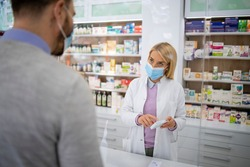 Female pharmacist selling vitamins and medicines to the customer in pharmacy shop during corona virus pandemic.
