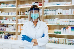 Female pharmacist with protective mask on her face working at pharmacy. Medical healthcare concept. Discount, sale concept.