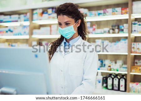 Female pharmacist with protective mask on her face working at pharmacy. Medical healthcare concept.