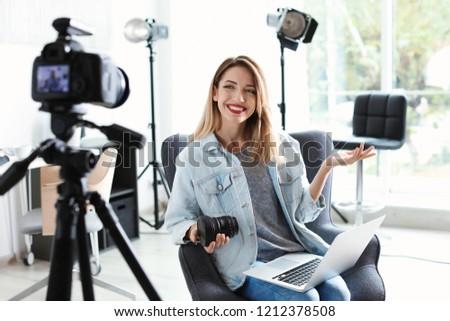 Female photo blogger recording video on camera indoors