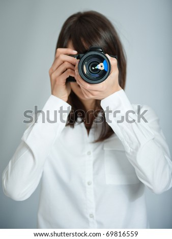 Female photographer aiming her camera at you