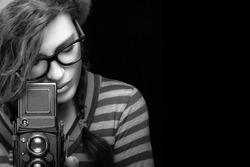 Female photographer. Close up Attractive Young Woman in Trendy Outfit Capturing Photo Using Vintage Camera. Black and White Portrait Isolated on Black Background with Copy Space.