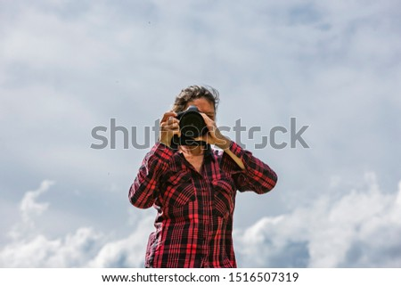 Female photographer in nature on a rock taking photos