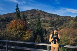 female photographer is looking at DSLR camera in autumn against backdrop of mountains.
