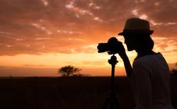 Female photographer outdoors capturing a beautiful sunset.