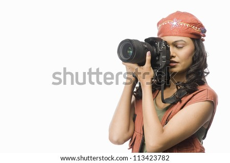 Female photographer photographing with digital camera
