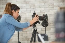 female photographer setting up camera in studio