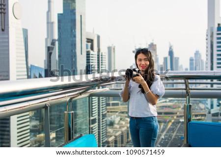 Female photographer taking picture of Dubai cityscape