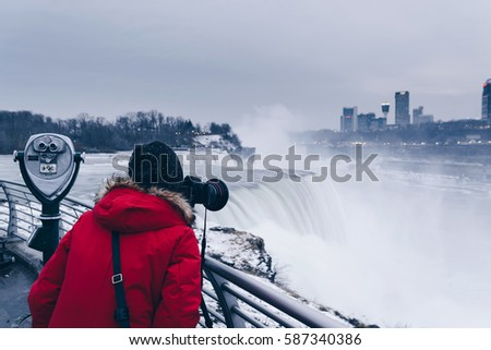 Female photographer taking pictures of Niagara Falls on a cold day